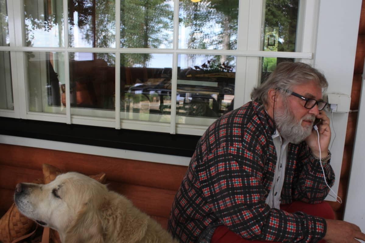 Kauko Salo vastaa puhelimeen mökillään, Elli-koira partioi vieressä.