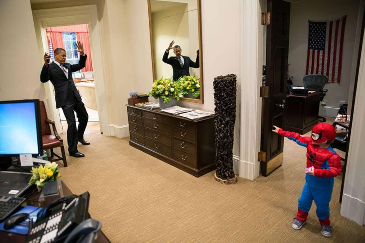 Barack Obama ja lapsi joka on pukeutunut hämähäkkimies-asuun