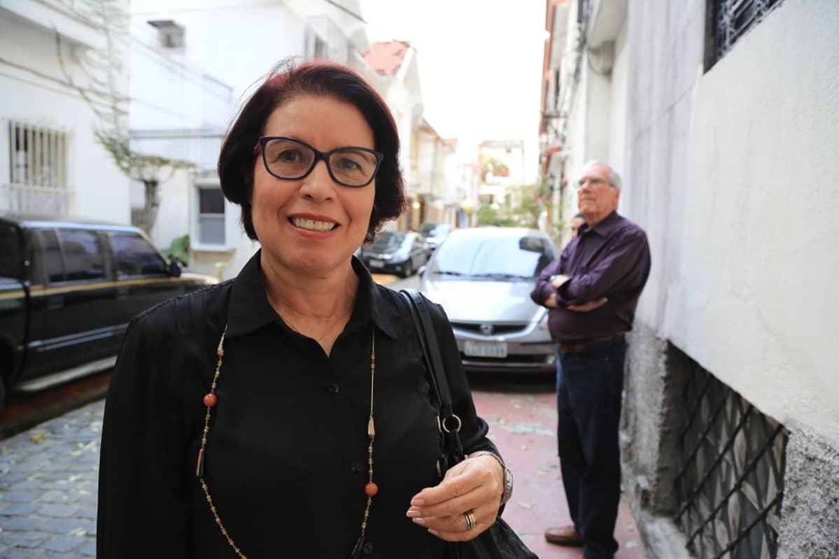 Vaaleaihoinen nainen, tummat lyhyet hiukset ja tummasankaiset silmälasit. Taustalla autoja ja taloja.