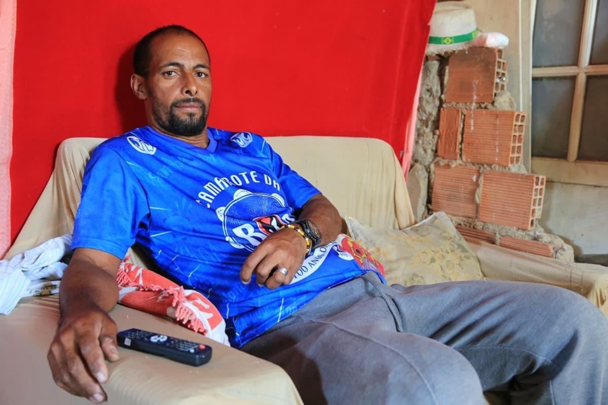 Parrakas mies sinisessa urheilupaidassa, istuu sohvalla.