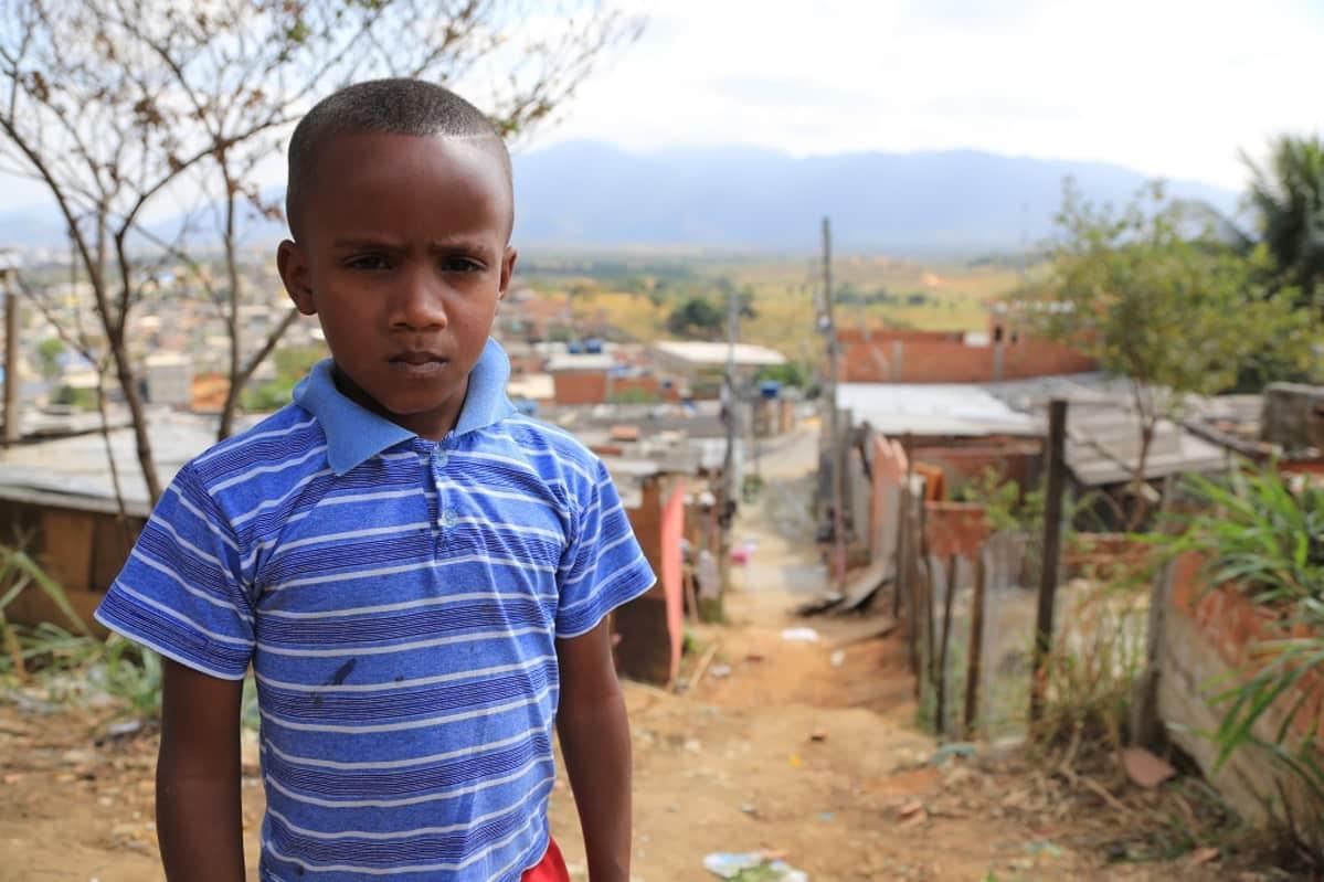 Pieni, siniseen paitaan pukeutunut tummaihoinen poika, katsoo kulmat kurtussa kameraan. Taustalla hiekkatie ja matalia, vaatimattomia taloja.