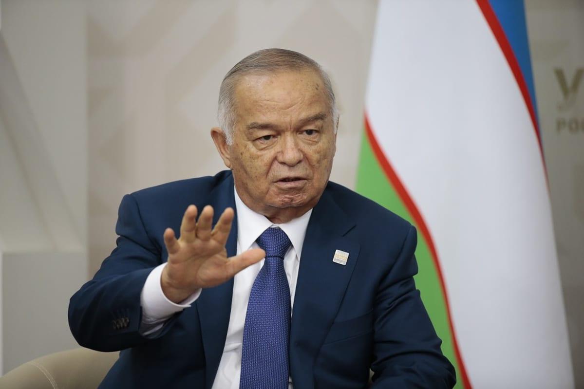 Karimov puhuu pitäen oikeaa kättään torjuvasti kämmen edessä. Hänellä on tummansininen puku ja kravatti. Taustalla näkyy Uzbekistanin lippu.