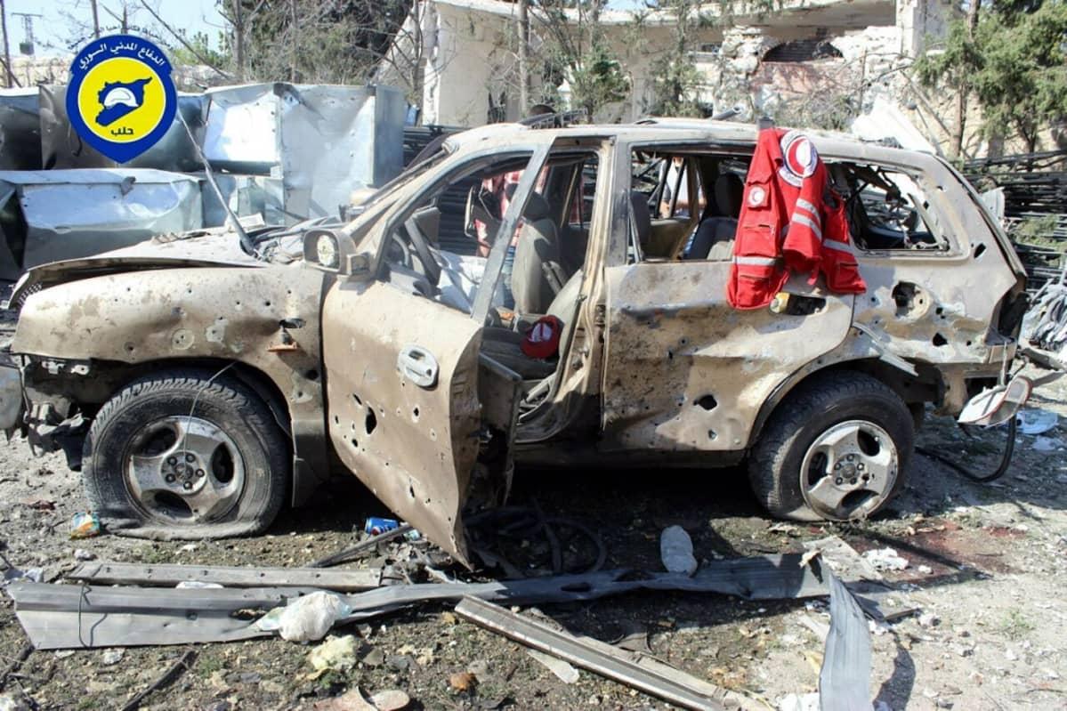 Ammusten runtelema henkilöauto raunoiden keskellä.
