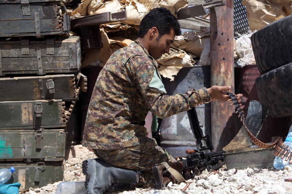 Maastopukuinen nuori sotilas on polvillaan maassa ja asettaa panosvyötä konekivääriin. Hänen ympärillään on ammuslaatikoita.