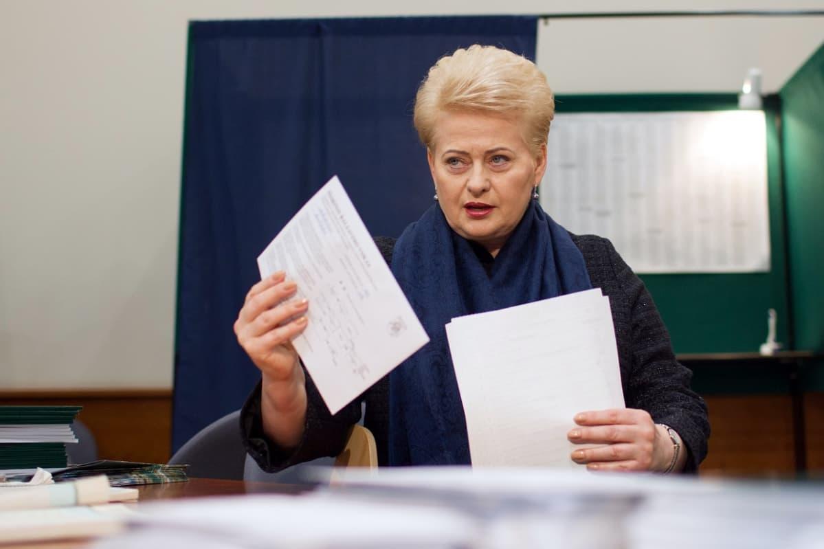 Presidentti äänetyslaatikon takana. Äänestyslipukkeet kädessä. Katse kameran suuntaan.