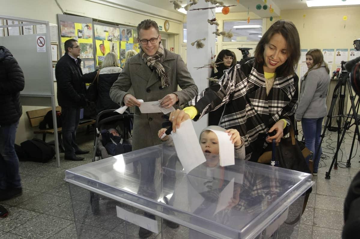 Nuoripari  lapsineen kouluun perustetussa vaalihuoneistossa. Lapsi pudottaa äänestyslippua läinäkyvään uurnaan.