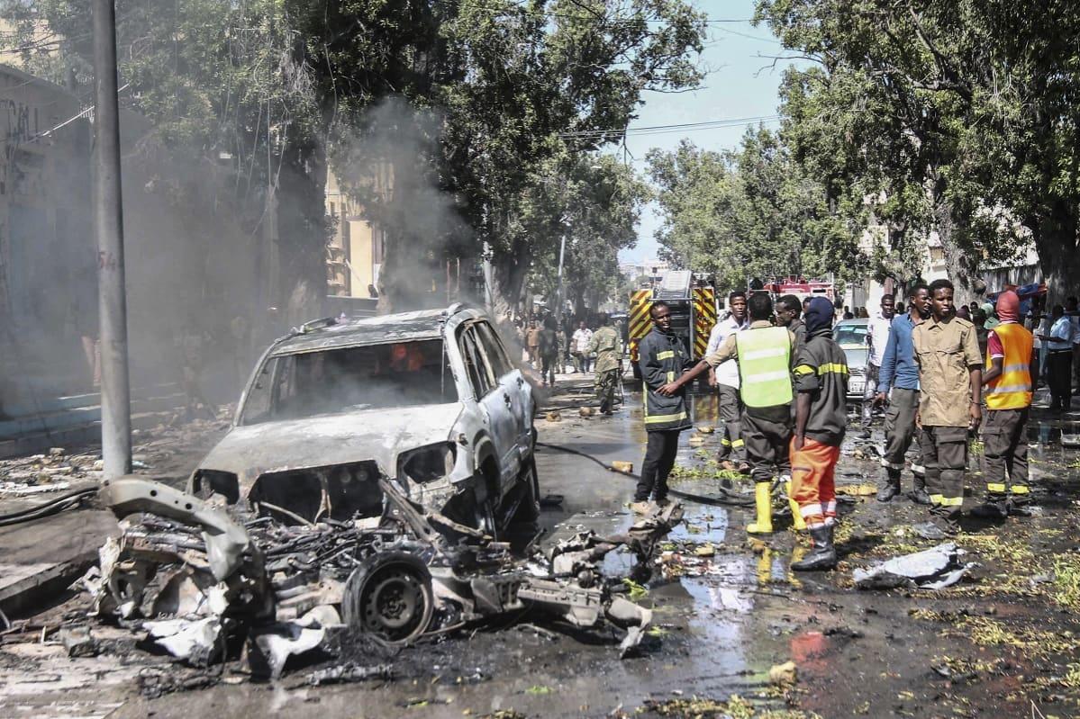 Savuava harmaa kasa metalliromua joukossa näkyy autonrengas, kasan vieressä on auto ja ihmisiä joilla on turvaliivejä päällä.