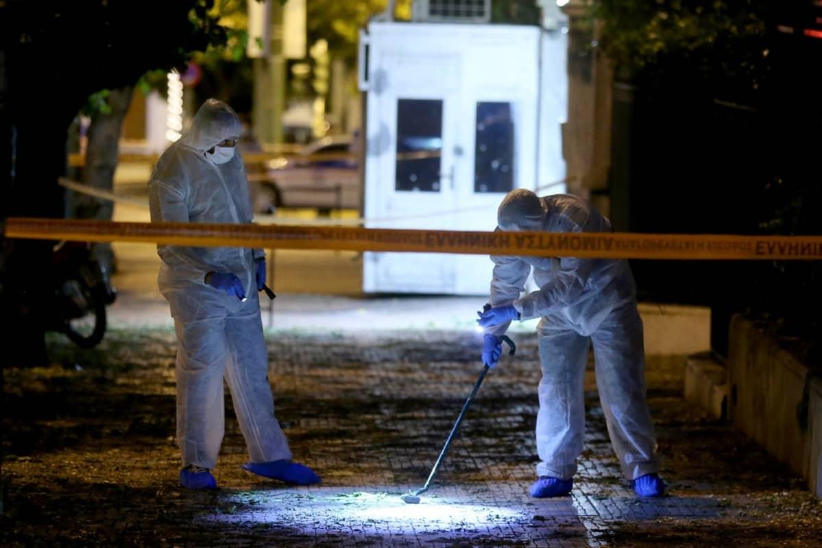 Suojahaalareihin pukeutuneet miehet tutkivat metallinpaljastimella katua, jonka poikki kulkee poliisin keltainen muovinauha.
