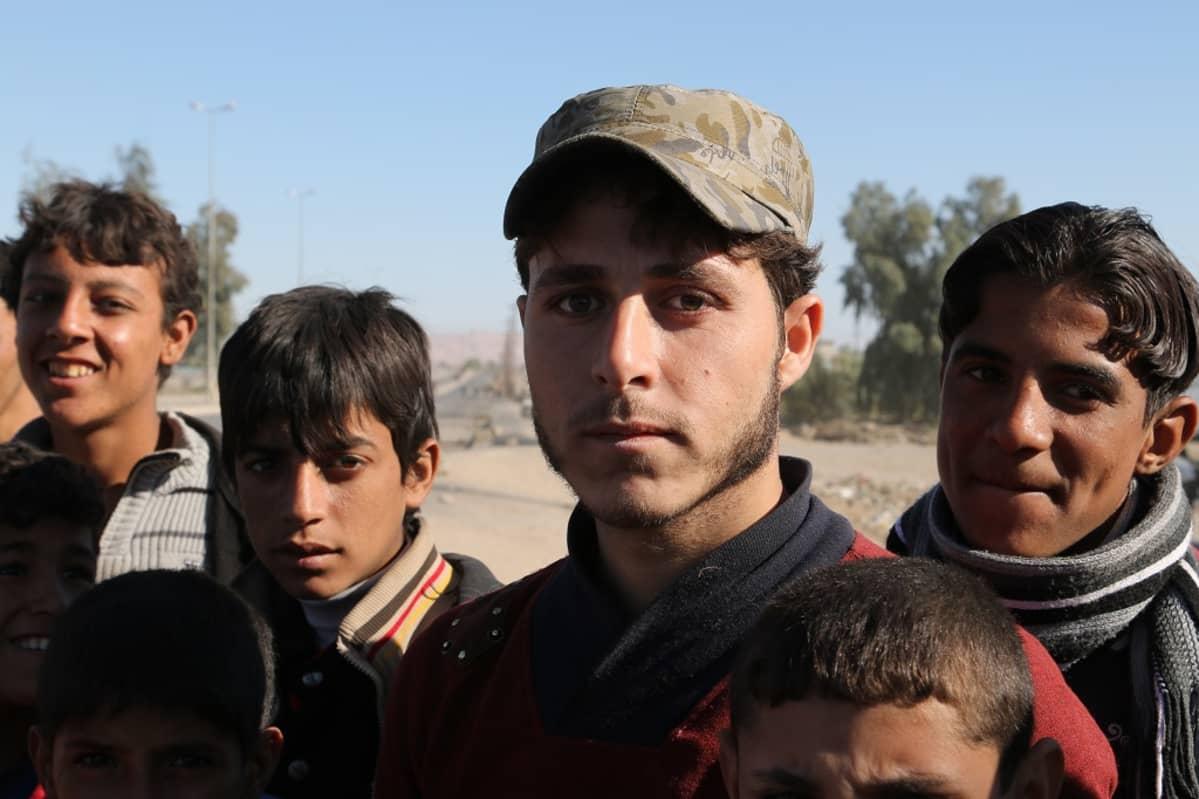Lippahattupäinen nuori mies katsoo kameraan. Vieressä nuoria poikia.