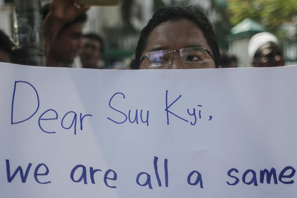 "Mies pitelee kylttiä, jossa lukee: ""Dear Suu Kyi, we are all a same."""