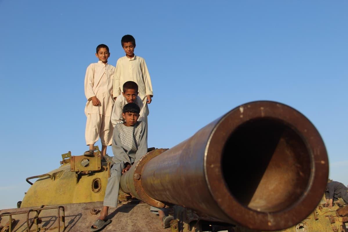 Afganistanilaislapset seisovat neuvostoaikaisen tykin päällä.