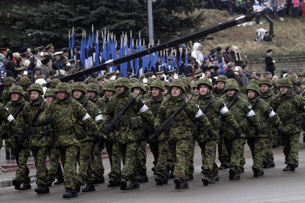 Vihreissä sotilasasuissa olevat sotilaat marssivat etualalla. Taustalla näkyy rivi Viron lippuja.