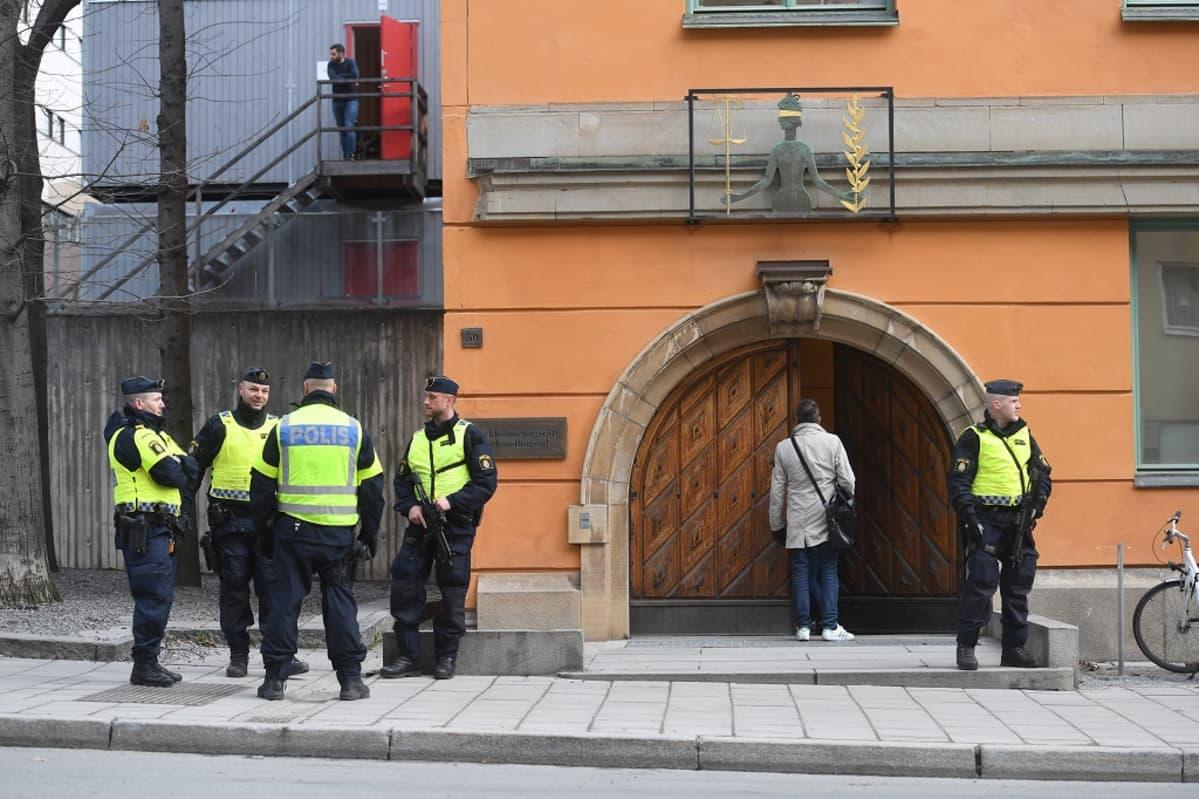 Neljä poliisia keltaisissa huomioliiveissä ja suikat päässään seisoo oranssinvärisen oikeustalon edessä kuvan vasemmalla laidalla. Yhdellä on kädessään konetuliase. Yksi poliisi seisoo oikeustalon oven oikealla puolella pitäen myös konetuliasetta ja katsoo oikealle.