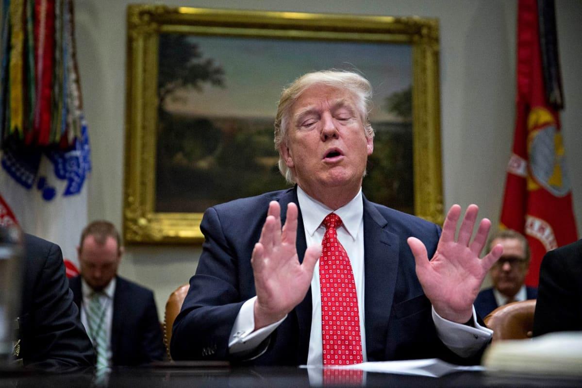 Presidentti Donald Trump istuu pöydän takana silmät kiinni ja kädet nostettuina eteen.