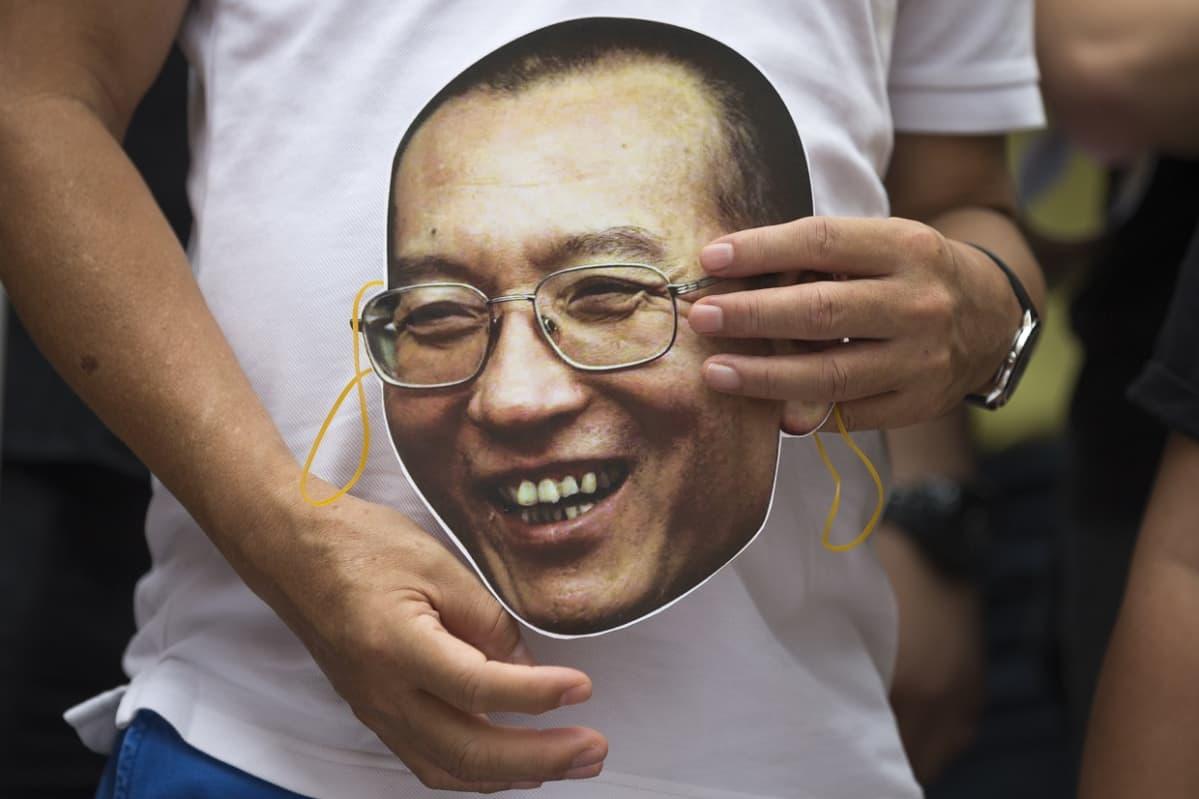 Liu Xiaobon kasvoja esittävä naamari mielenosoittajan käsissä.