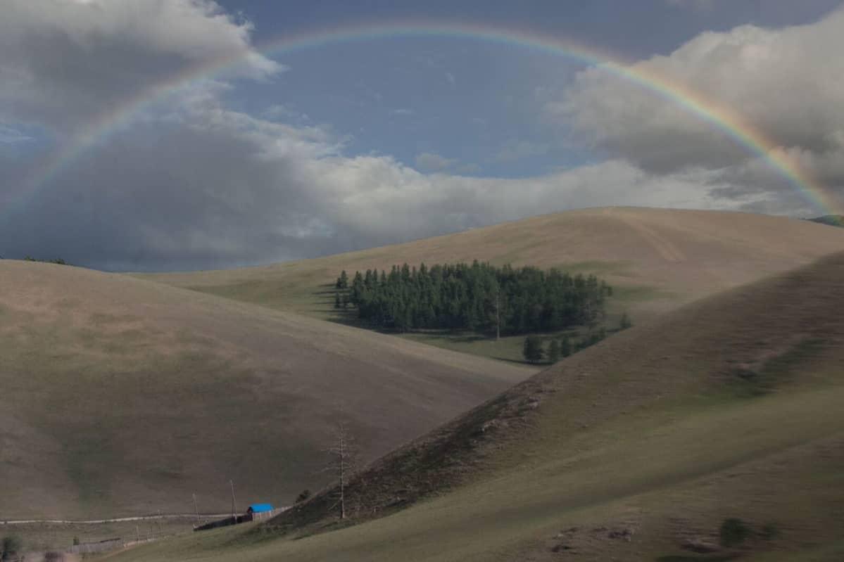 Sininen talo Mongolian aavikolla ja taivaalla sateenkaari