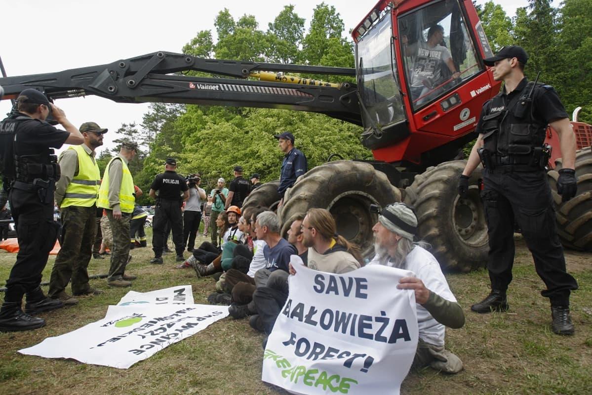 Joukko aktivisteja istuu maassa kaivinkoneen edessä. Ympärillä on poliiseja ja muita viranomaisia. Taustalla näkyy metsää.