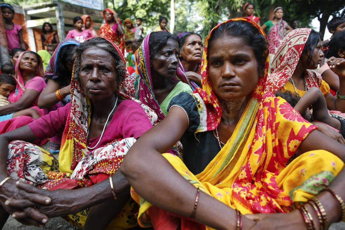Joukko naisia istuu värikkäät sarit päällä, totisina.