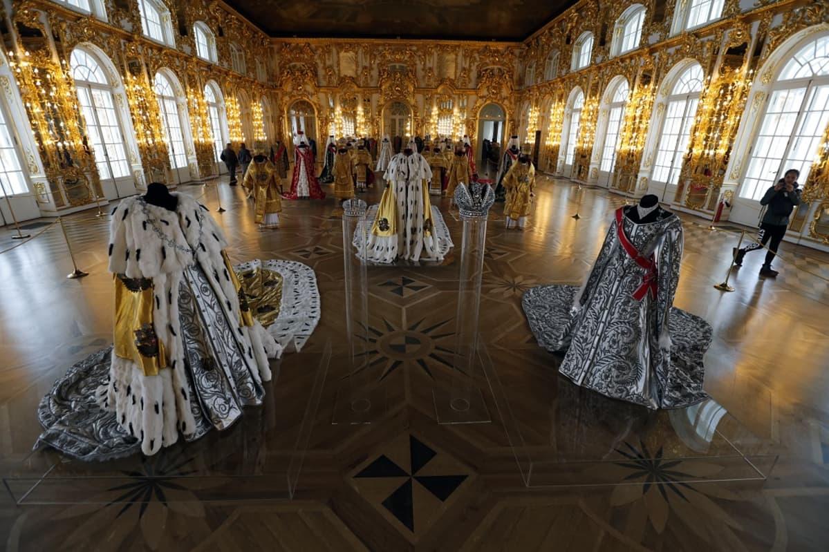 Tsaarien ja tsaarittarien koristeellisia asuja on esillä salissa, jonka seinät hehkuvat kullankeltaisina.