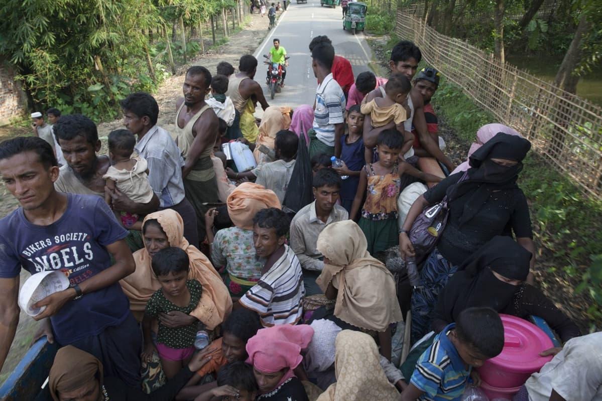 Suuri joukko pakolaisia seisoo ja istuu kuorma-auton lavalla. Taustalla autoa seuraa mies mopolla.