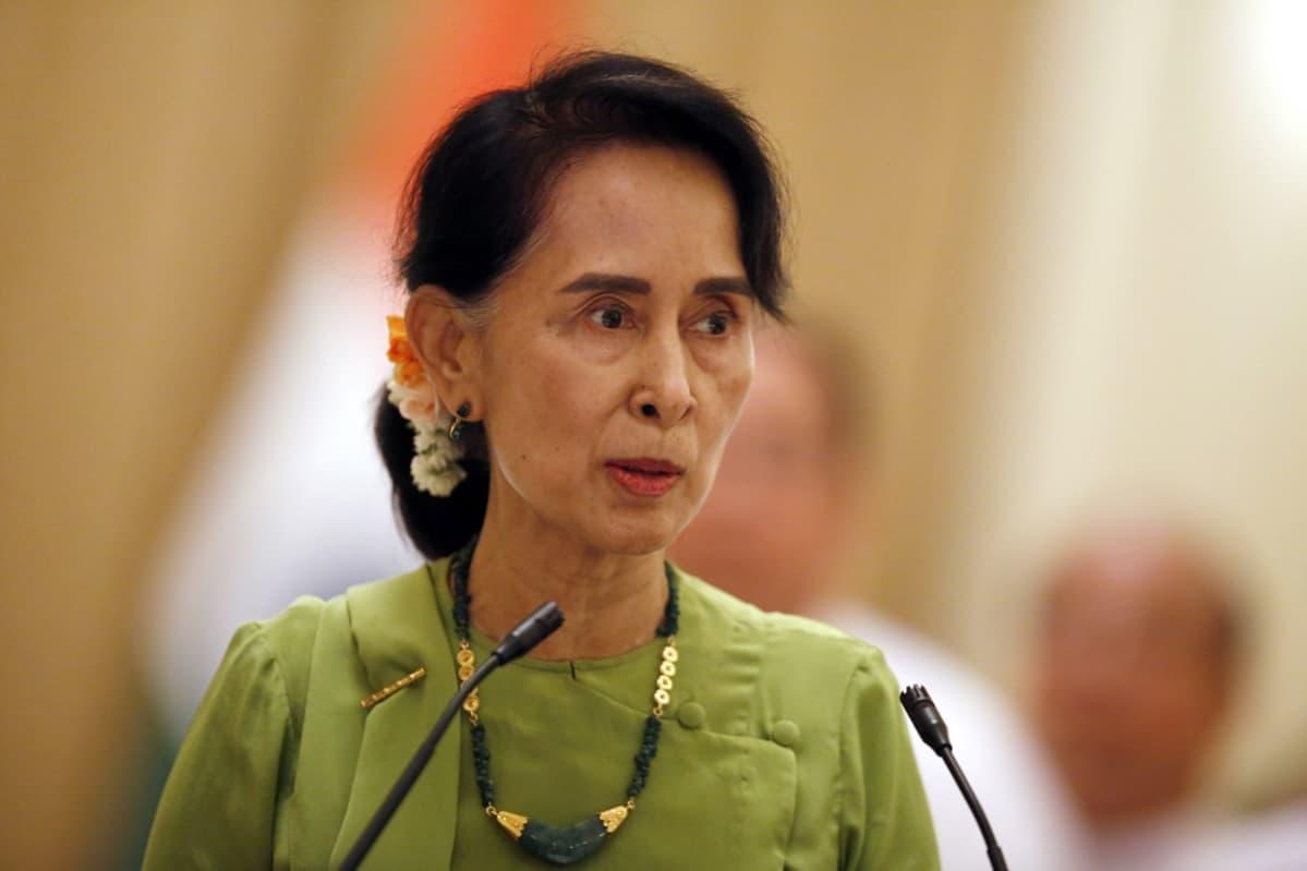 Aung San Suu Kyi vaaleanvihreässä asussa puhuu edessään oleviin mikrofoneihin.