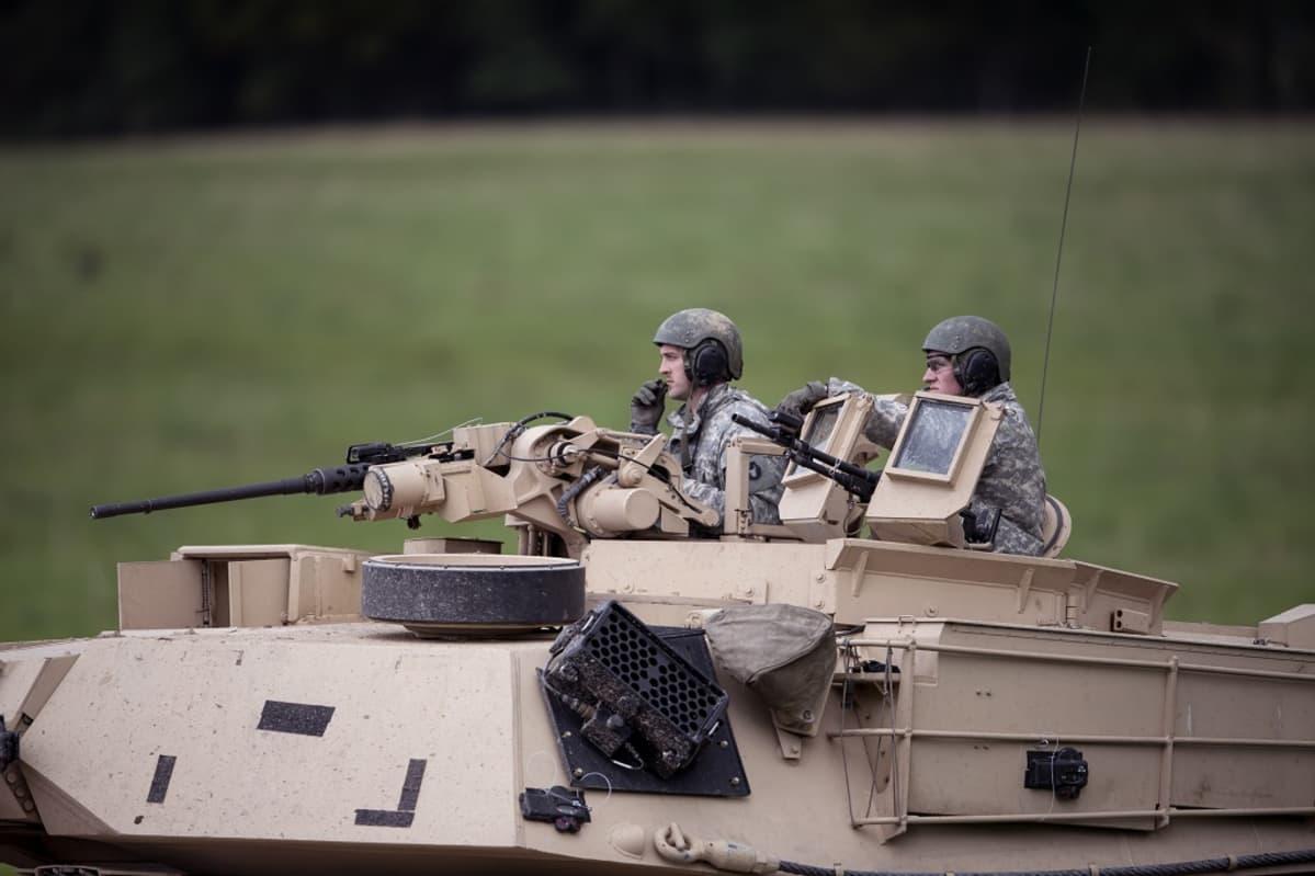 Kuvassa tankki ja kaksi sotilasta Aurora 2017-sotaharjoituksessa.