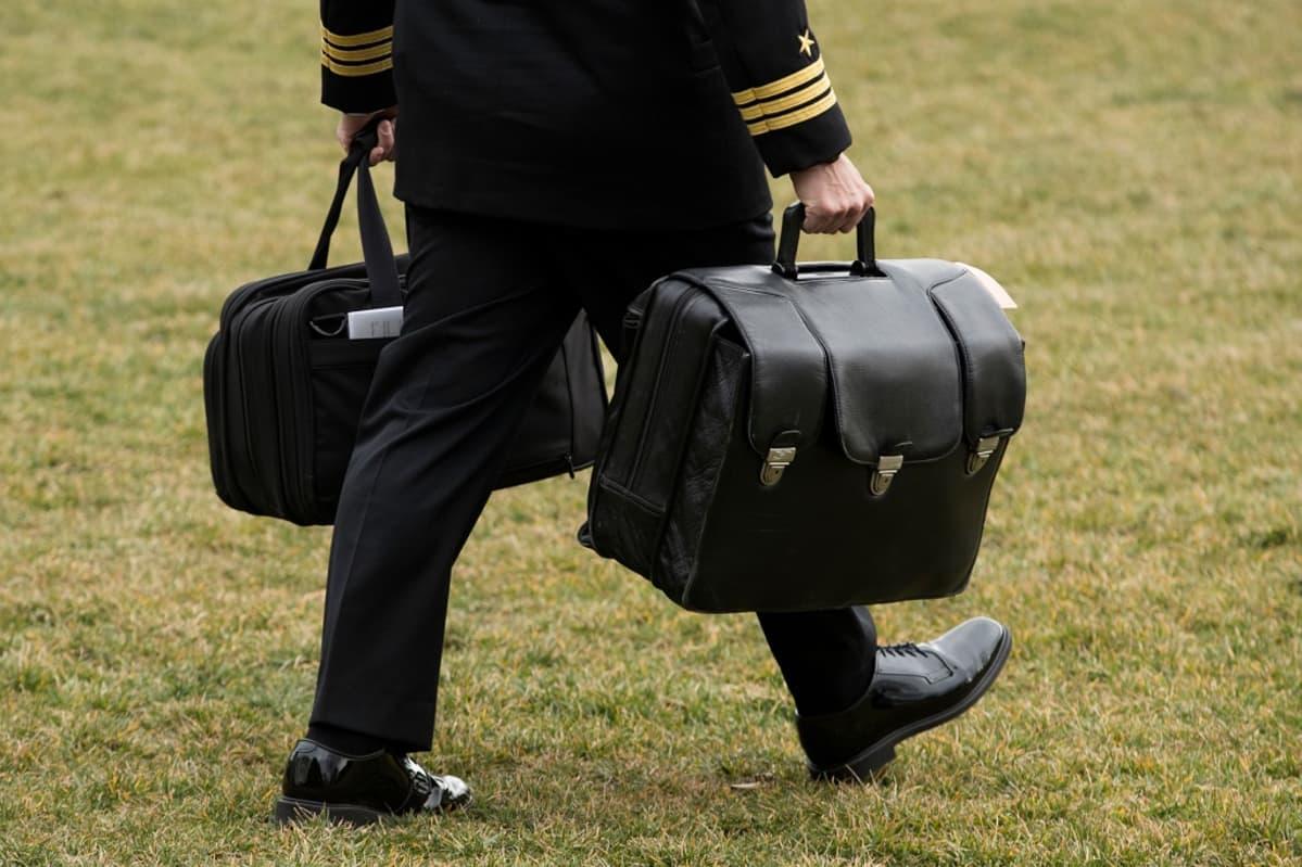 Mies kantaa kahta suurta salkkua.