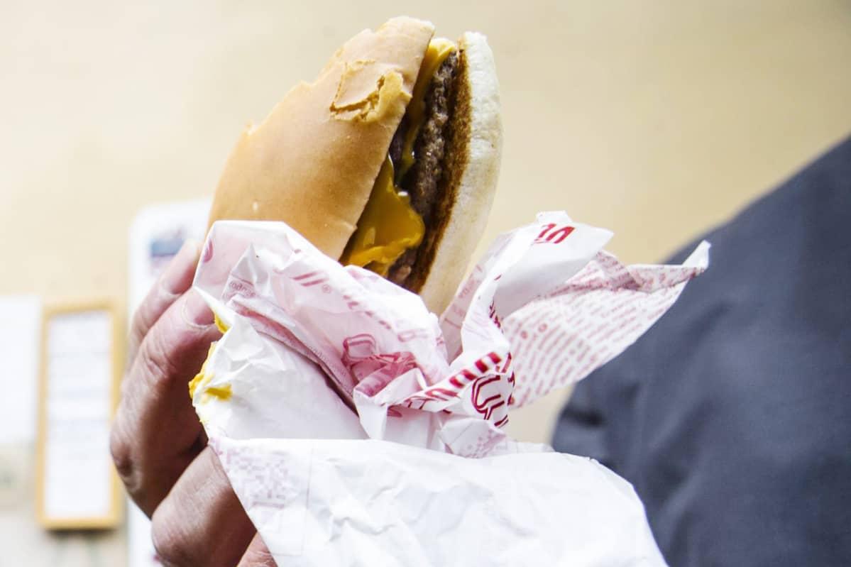 Mies syö hampurilaista.