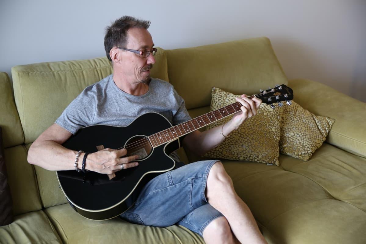 Kristian Olin istuu sohvalla ja soittaa akustista kitaraa.