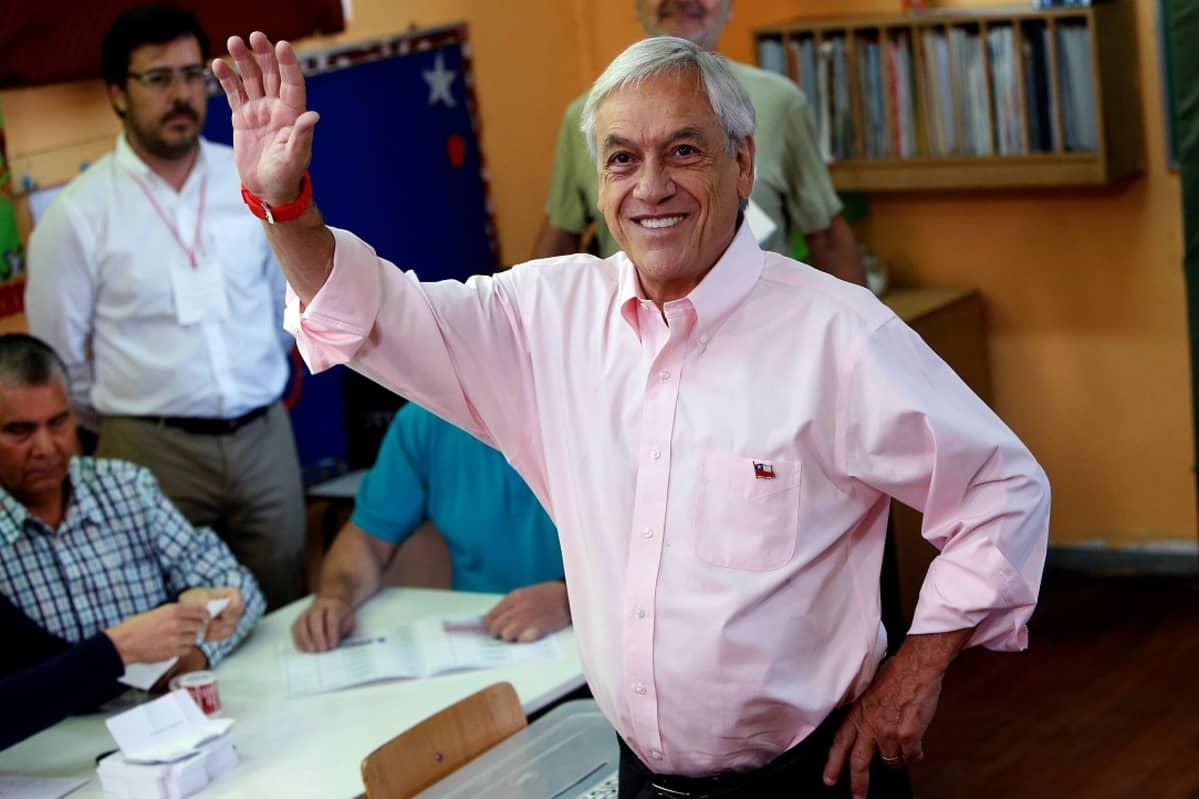 Harmaa hiuksinen mies, jolla on pinkki paita vilkuuttaa hymyilleen kameran suuntaan.