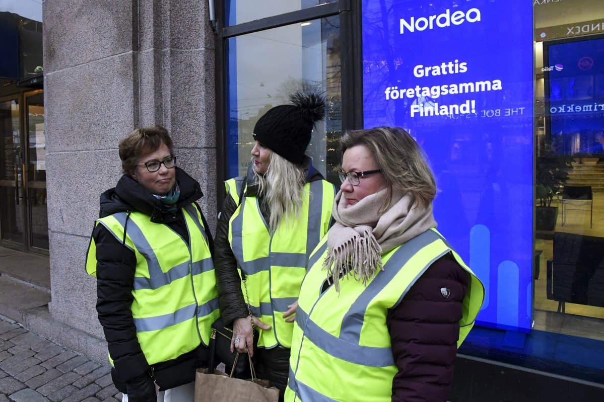 Lakkovahdit Minna Rytkönen (vas.), Minna Hamare (kesk.) ja Eija Mustonen suljetun Nordea-konttorin edessä Mannerheimintiellä Helsingissä torstaina 28. joulukuuta.