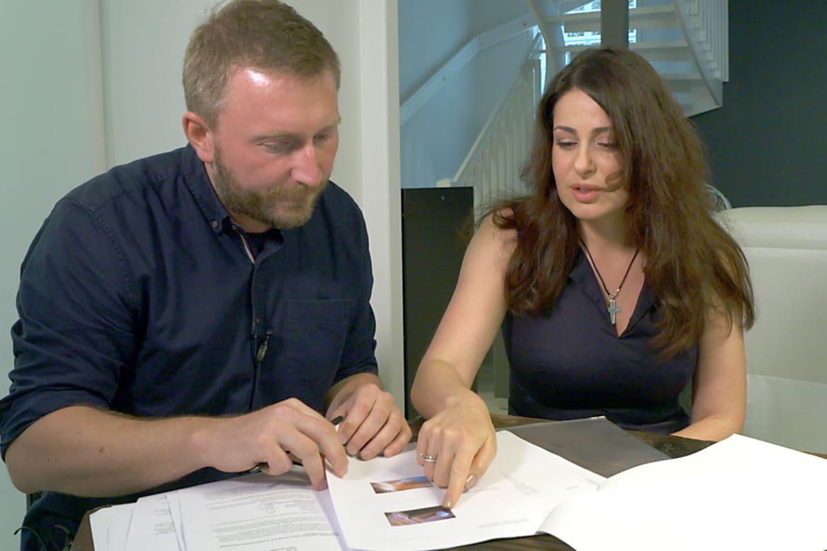Yles reporter sitter med en ca 40-årig kvinna vid ett bord inomhus och tittar på bilder i en rapport.
