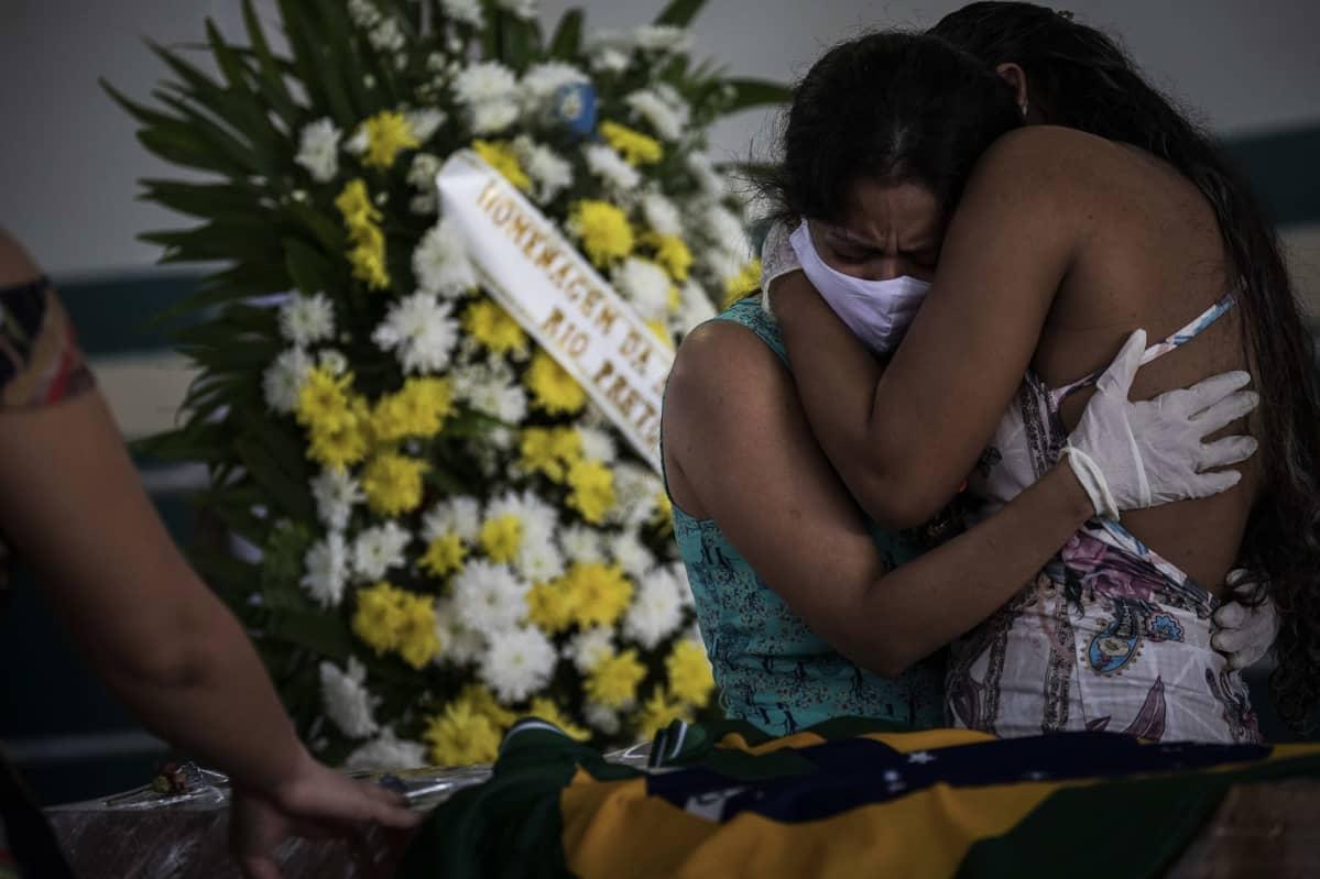 Naiset halaavat ruumisarkun äärellä.