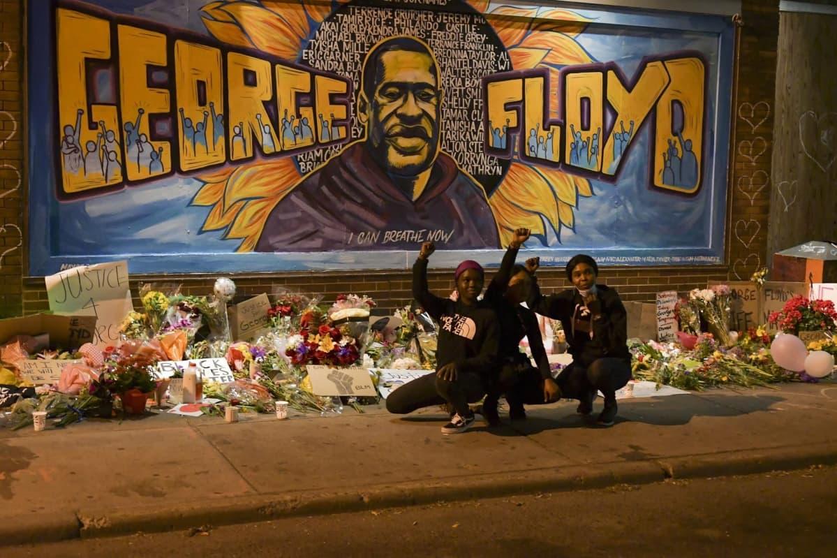 George Floydia esittävä seinämaalaus. Sen eteen on tuotu kukkia. Kolme nuorta poseeraa edessä.