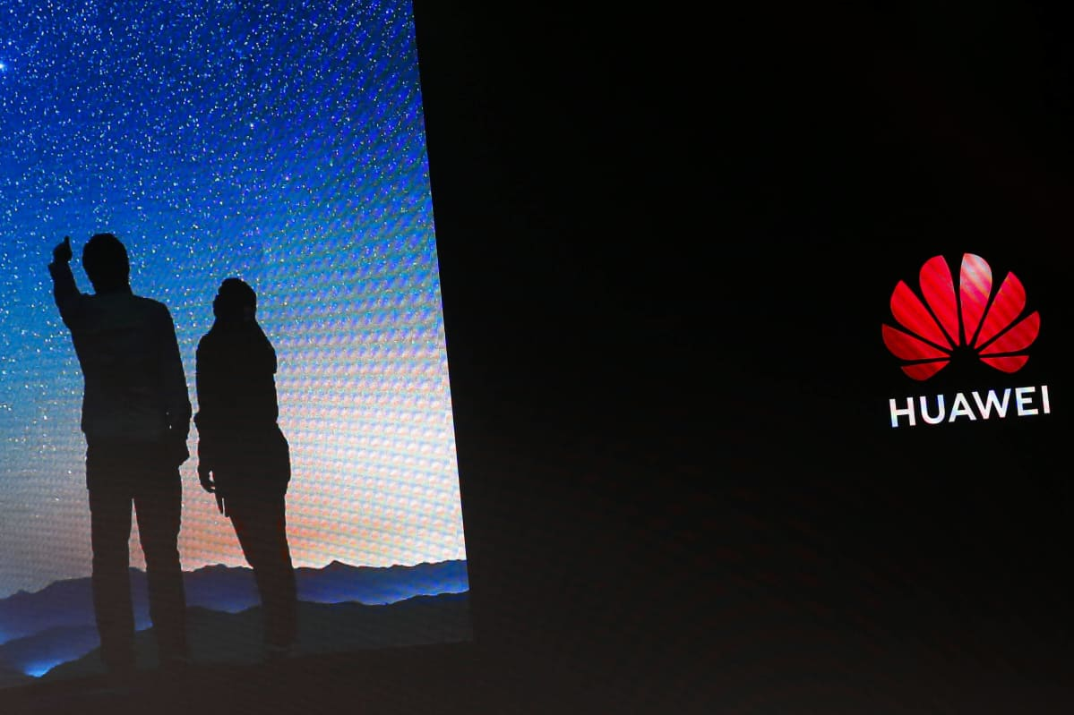 Huawein logo ja kaksi varjossa olevaa ihmishahmoa.
