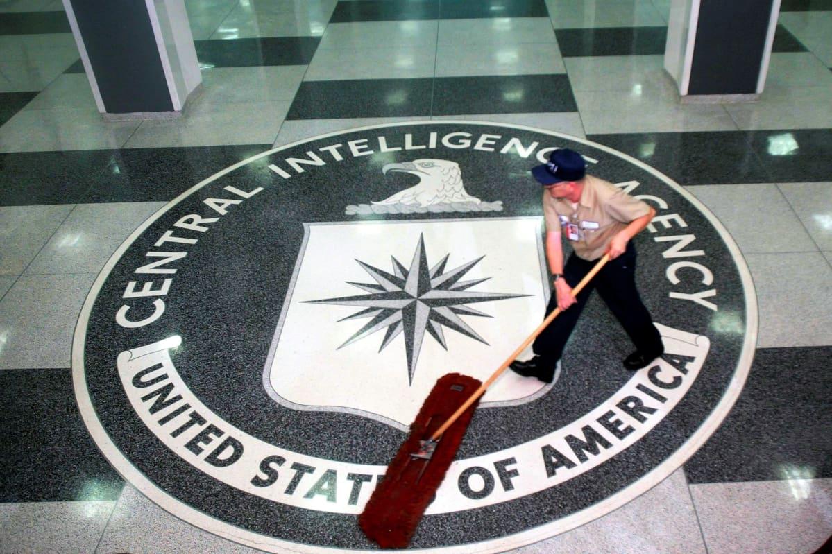 Univormupukuinen mies lakaisee lattiaa. Lattiassa on Yhdysvaltain keskustiedustelupalvelun CIA:n sinetti.