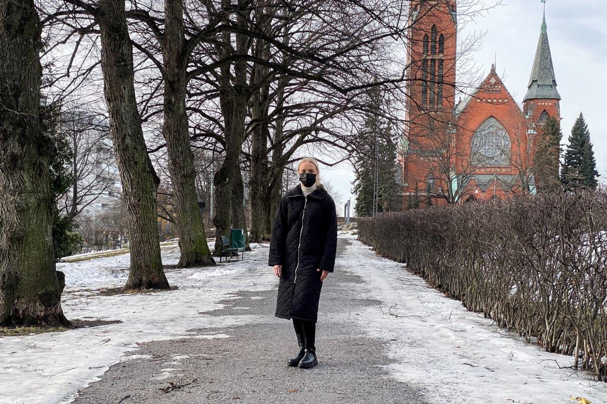 Nainen seisoo Mikaelinpuistossa Turussa.