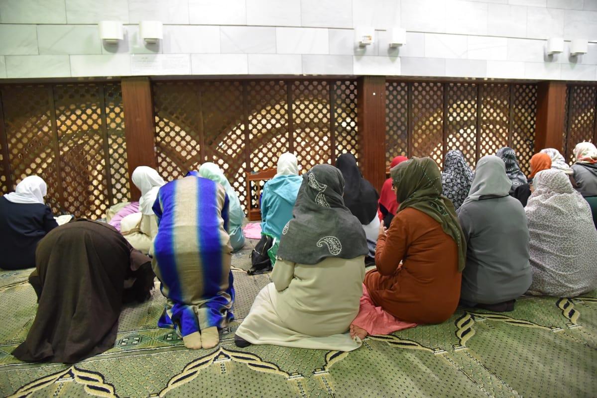 Hunnutetut naiset istuvat selin mattoon verhotulla lattialla edessään tähtikuvioinen säleikkö