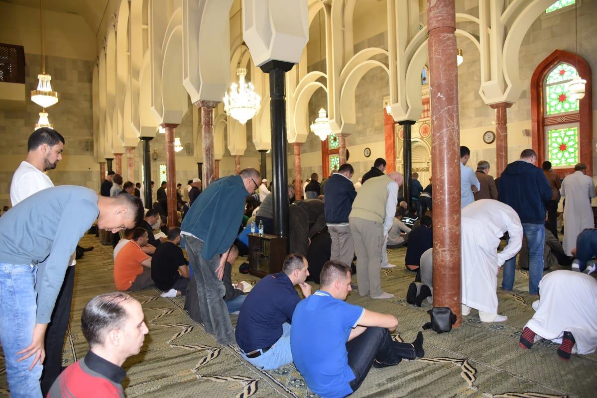 Kymmenet miehet rukoilevat marmoripylväiden välissä.
