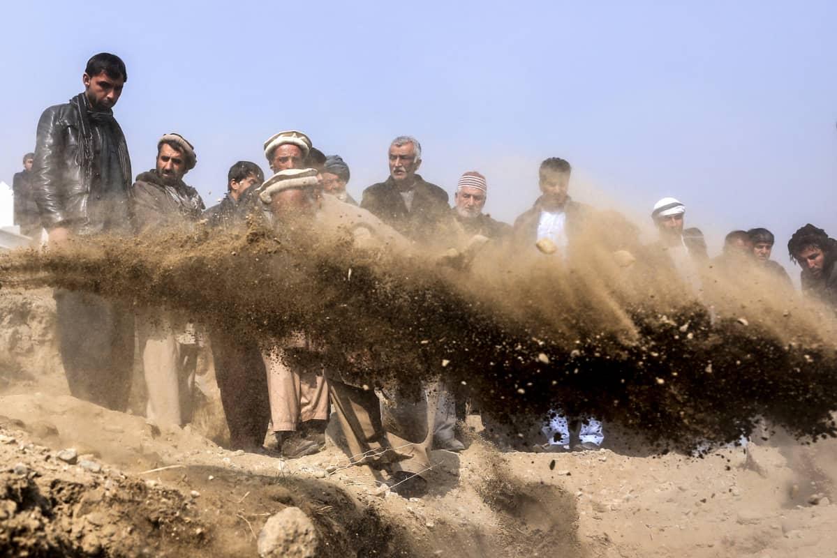 Kabulin pommi-iskun uhrien omaisia hautajaisissa heittämässä hiekkaa hautaan