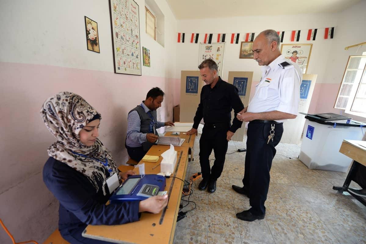 Kuvassa kaksi sotilasta äänestämässä Irakin Bagdadissa. Pöydän takana istuu kaksi vaalivirkailijaa.