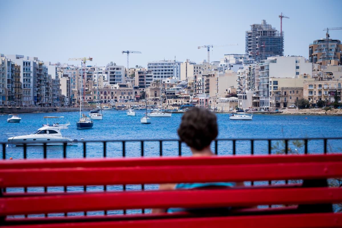 Nainen istuu penkillä rannassa, takana kaupunkisiluetti, jossa nostokurkia