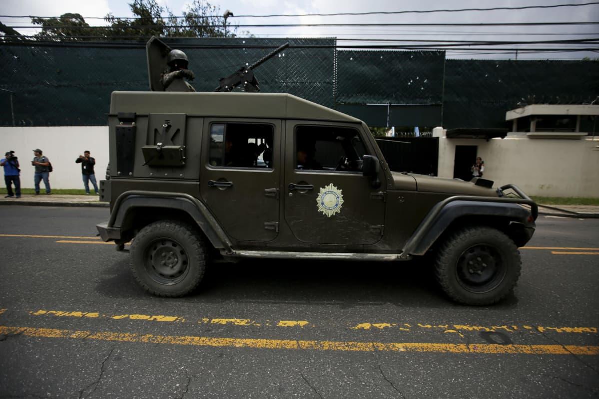 Kuvassa armeijan jeeppi, jonka kattoluukusta kurkistaa kypäräpäinen sotilas ase tanassa.