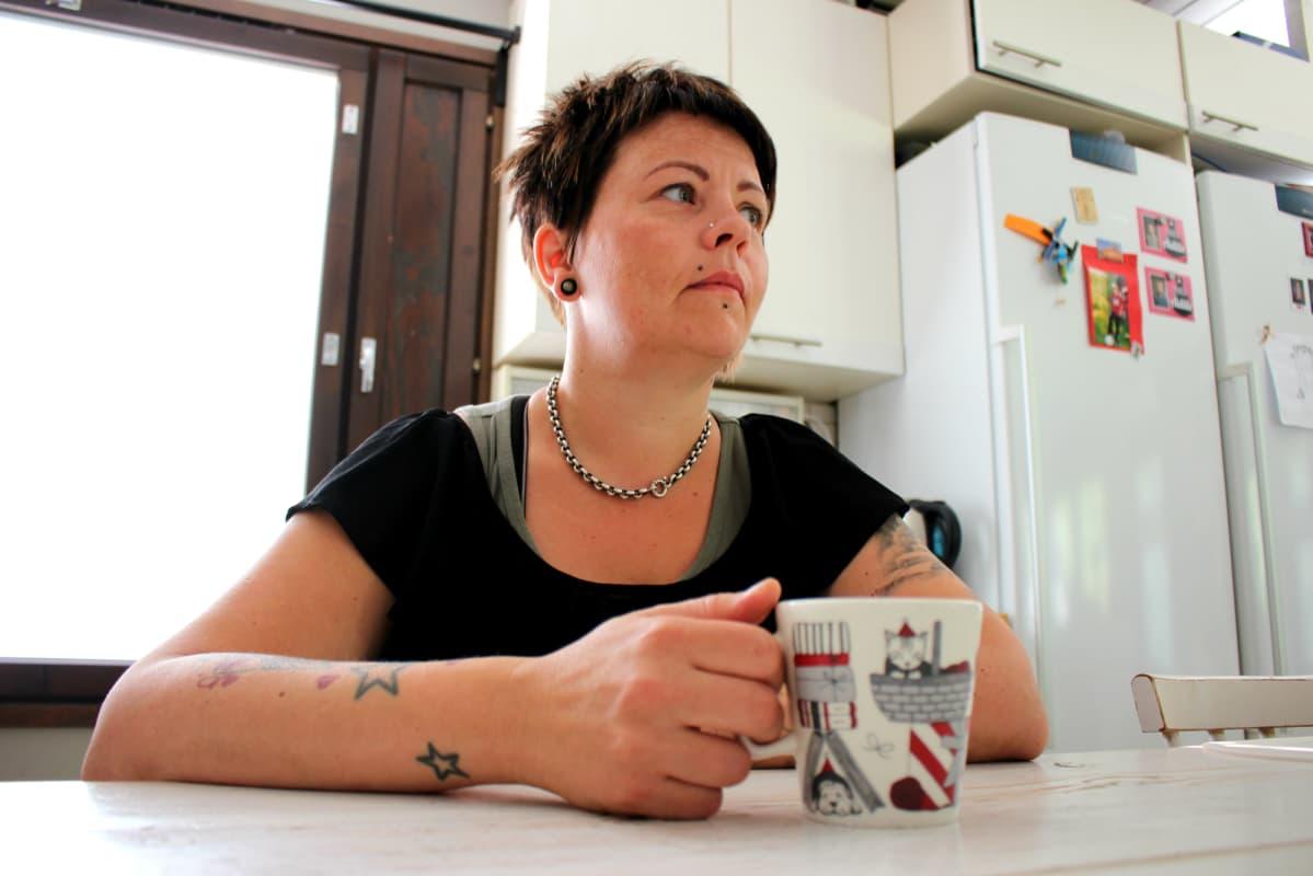 Mervi Heino juo kahvia keittiössään.