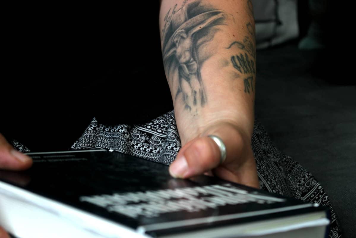 Mervi Heino pitää kädessään Anonyymien Alkoholistien kirjaa. Käteen on tatioitu risti uskontunnustukseksi.