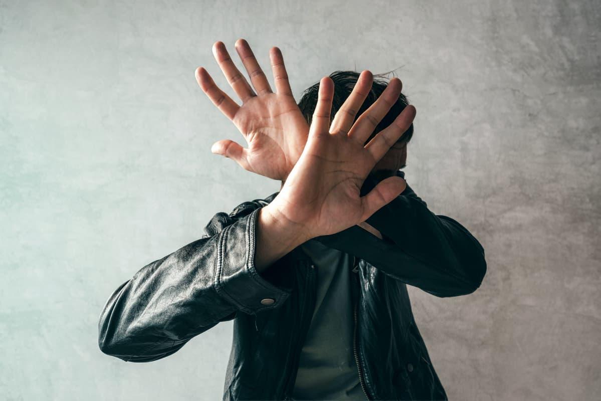 mies suojaa käsillä kasvojaan