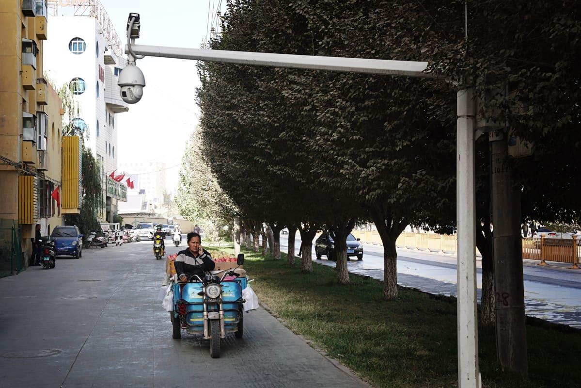 valvontakamera kadun yllä, kadulla nainen mopon selässä