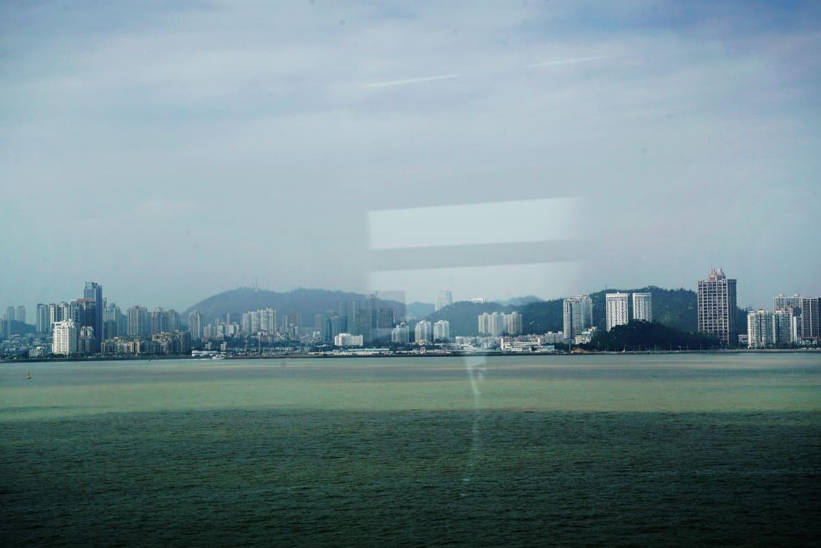 Zhuhain siluetti siintää bussin ikkunasta.