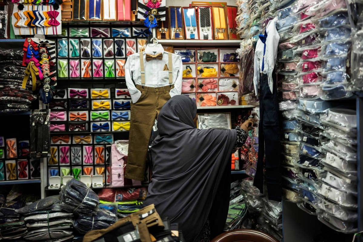 Muna Musa järjestää vaatteita kaupassa.