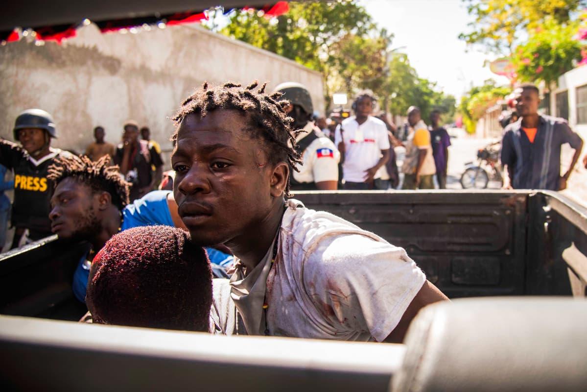 Poliisit kuljettavat mielenosoituksissa loukkaantuneita kansalaisia.